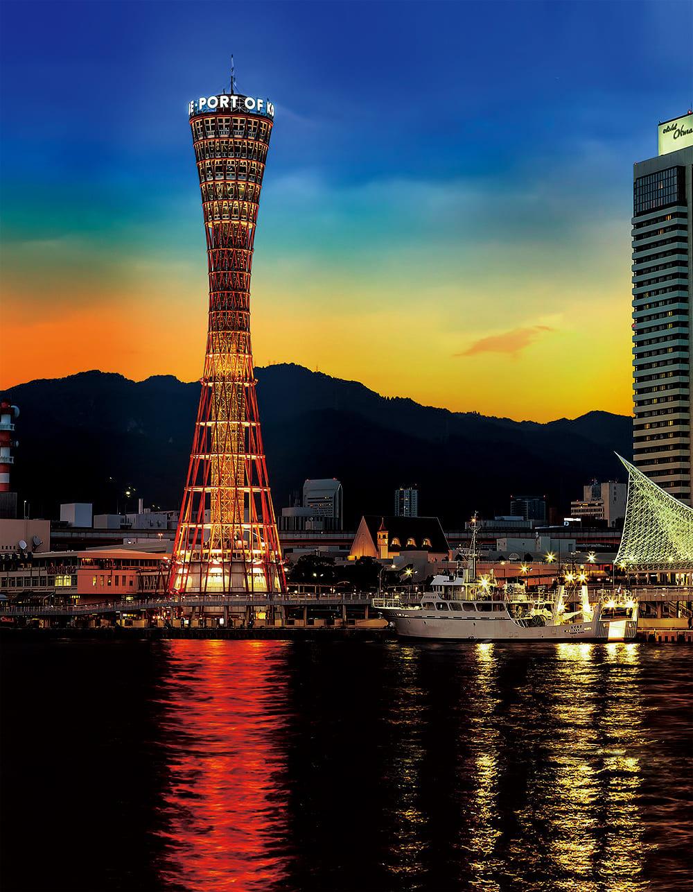 夕暮れの神戸ポートタワーと海。背後には六甲山の風景が広がっています。
