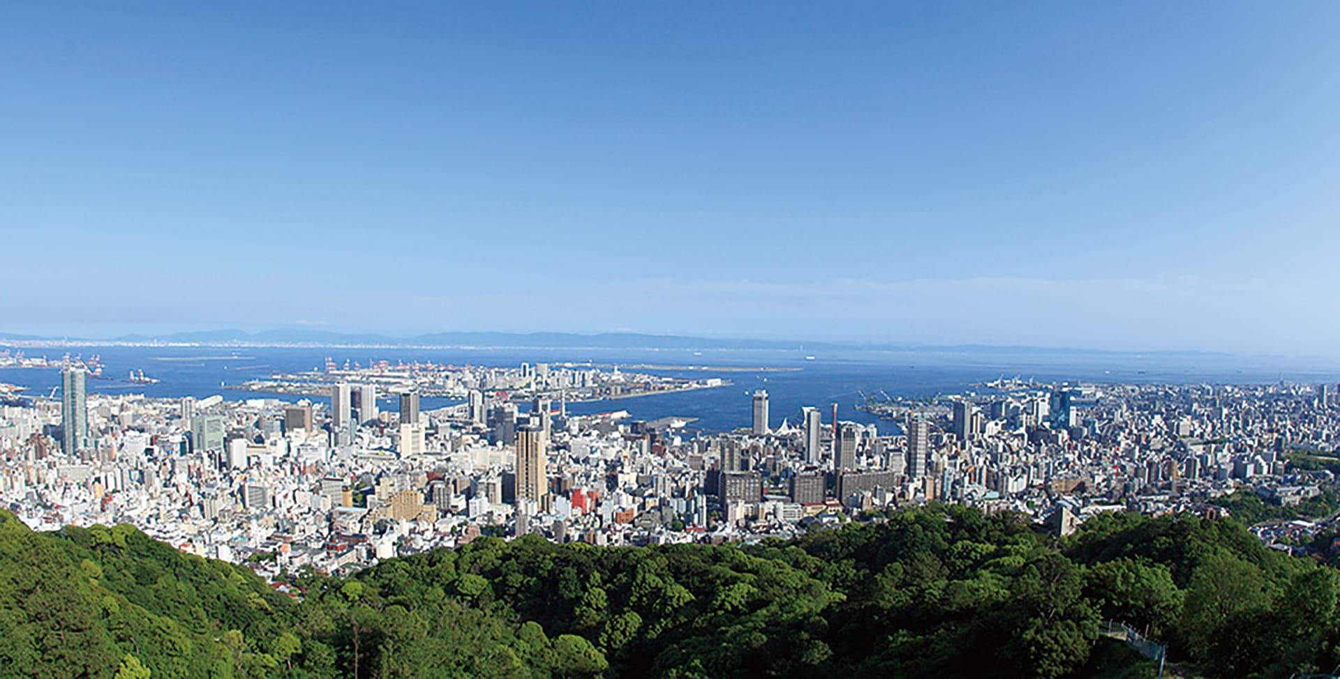 六甲山行きの急行バスから見た六甲山の緑の先には神戸の街並み。その奥には海が見えます。