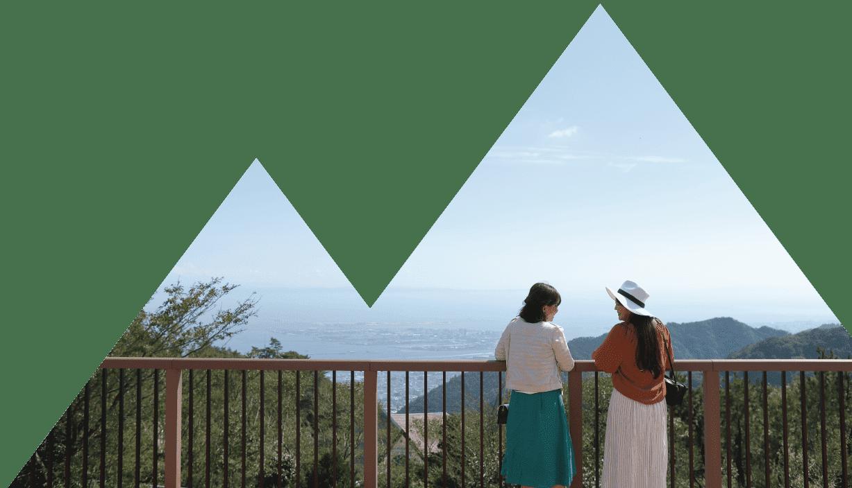 女性二人組みの観光客が六甲山上から神戸の街並みを眺めています。