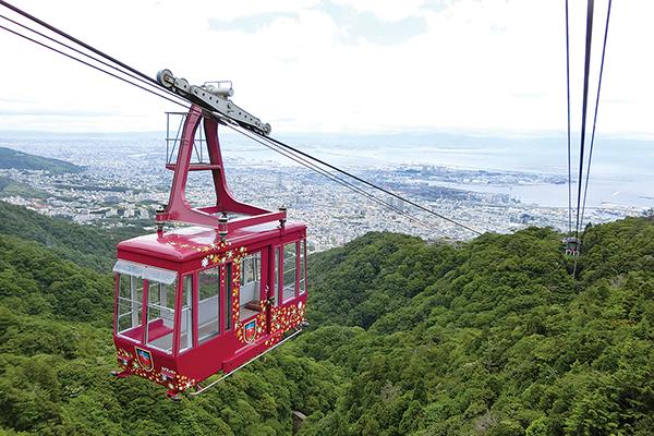 六甲山上から見た摩耶ビューラインロープウェイと神戸の街並み。その奥には海が見えます。