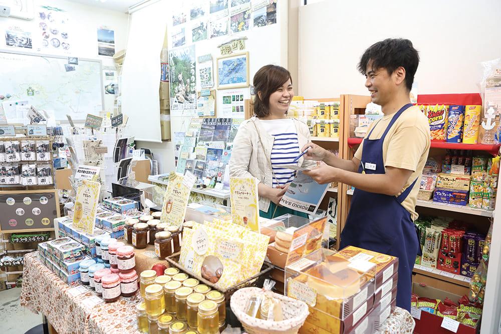 653cafe 六甲遊山案内処で女性の観光客が店員と話をしています。